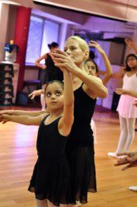 Ballet teacher correcting student